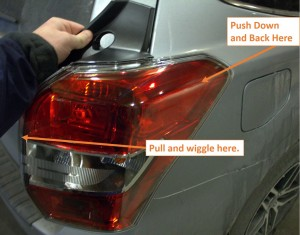 The photo shows where to push and pull on the taillight of a subaru forester if it is stuck.